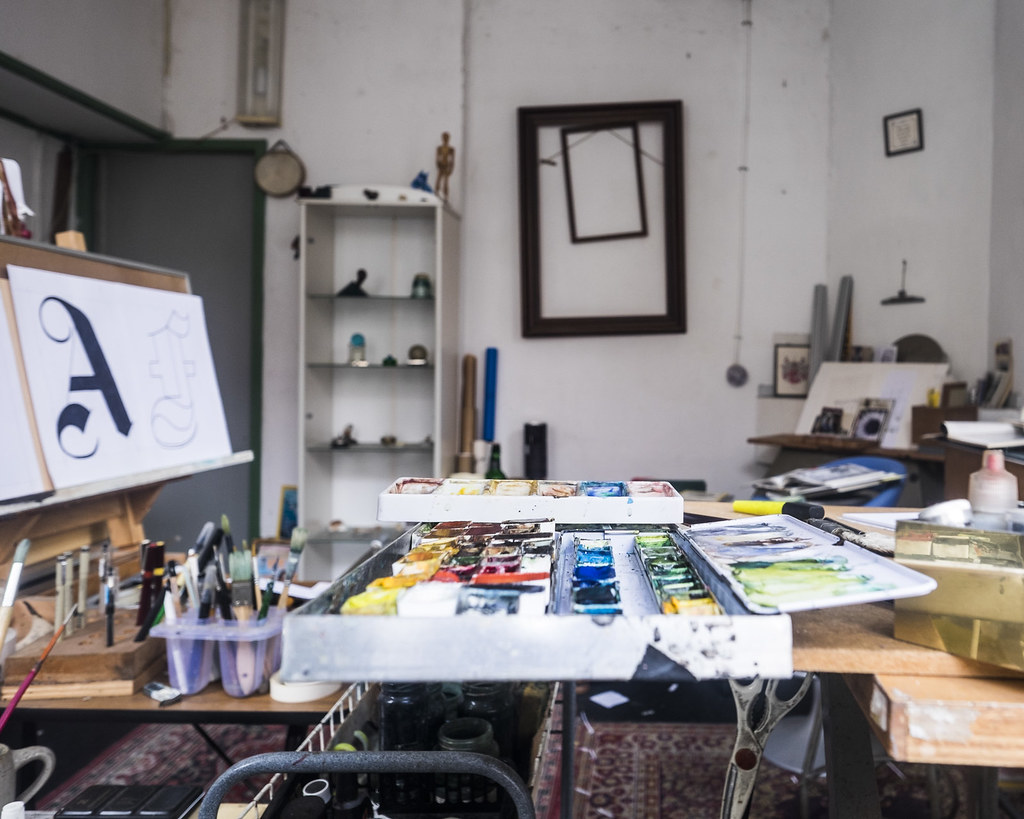 Artist's studio with canvases along the wall and paint and brushes on a table in the foreground.