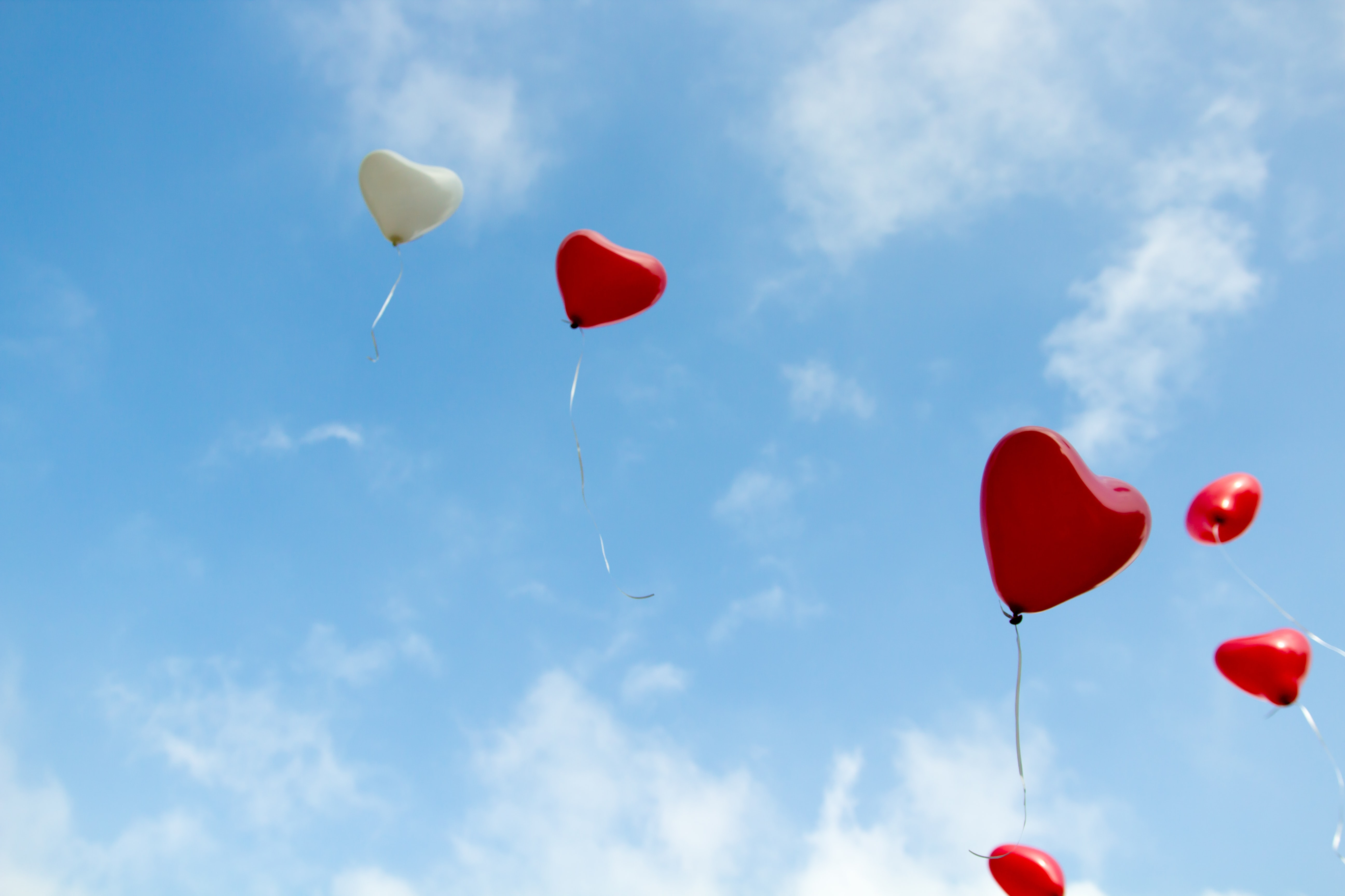Heart-shaped balloons float across a blue sky with few clouds.