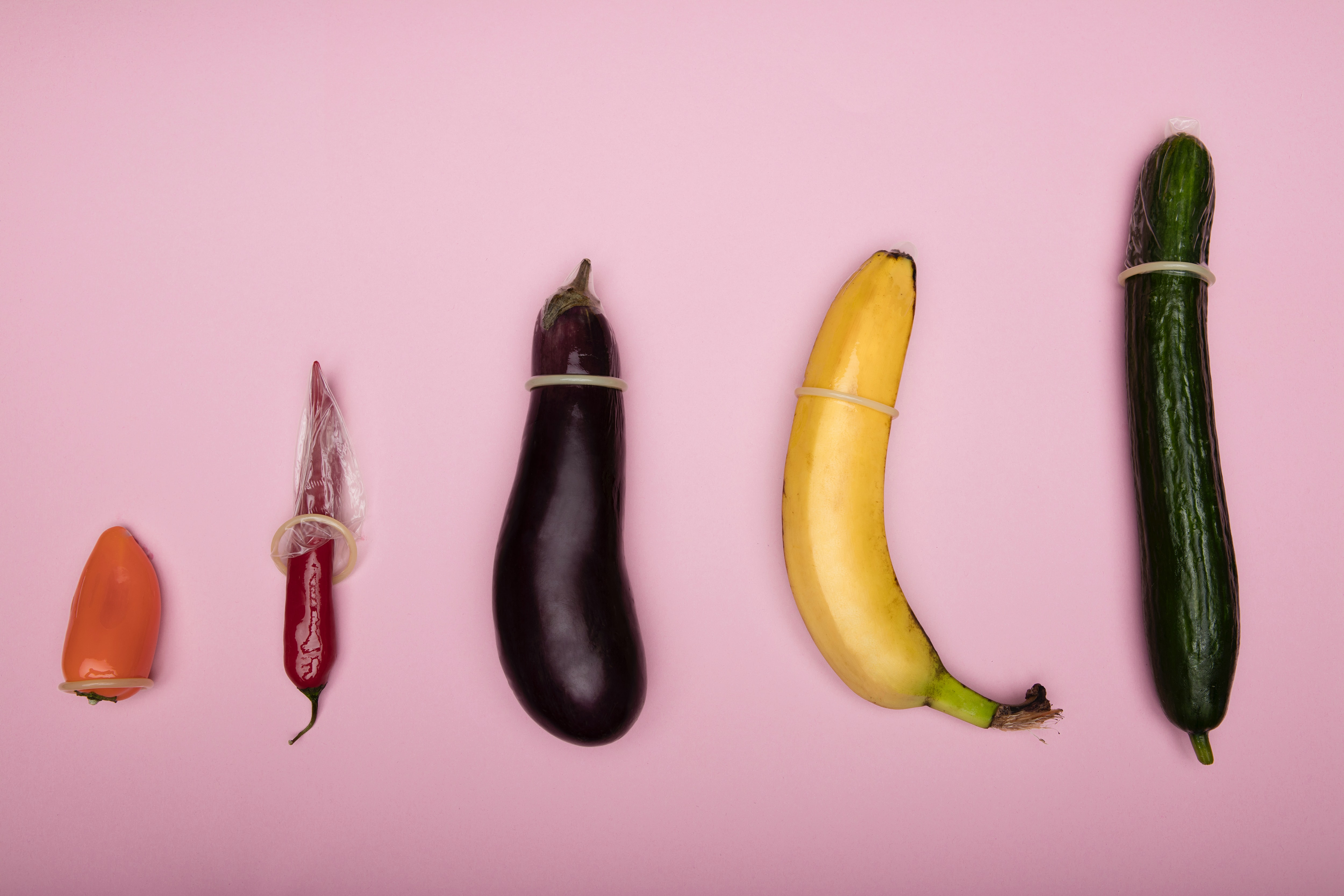 Two peppers, an eggplant, a banana, and a cucumber, all with condoms on, sit on a pink background.