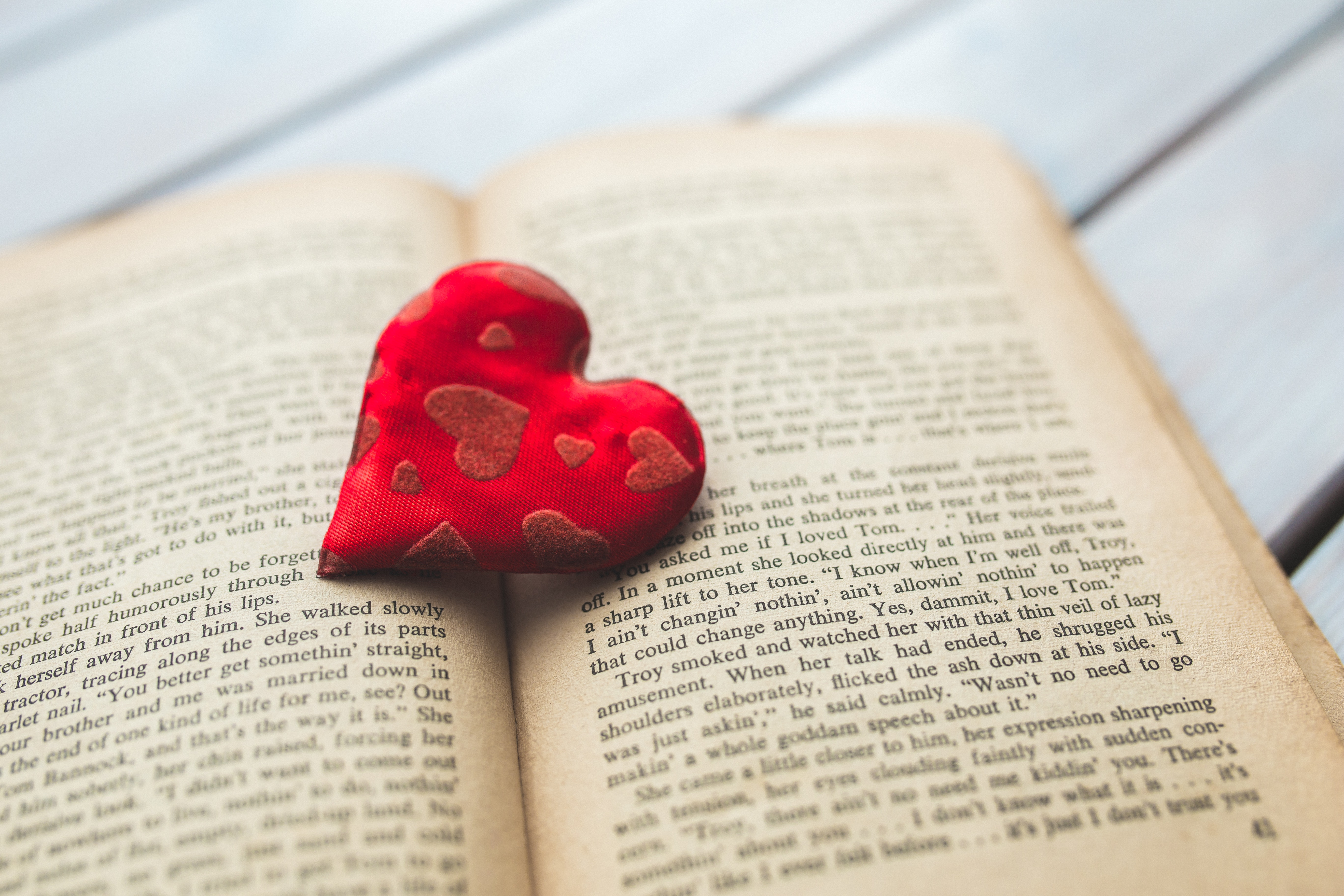 A small red heart lies on the pages of an open book.