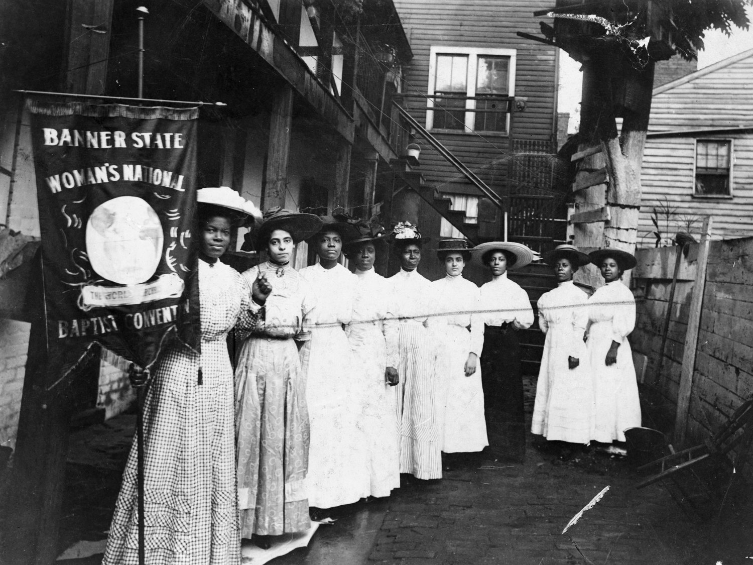 """Nannie Helen Burroughs, holding a banner reading, """"Banner State Woman's National Baptist Convention,"""" stands with eight otherAfrican-American women, photographed between 1905 and 1915. Burroughs (1879-1961) was an activist, educator and suffragette who fought for African American and women's rights."""