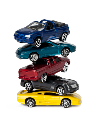 Five toy cars and trucks stacked on top pf each other