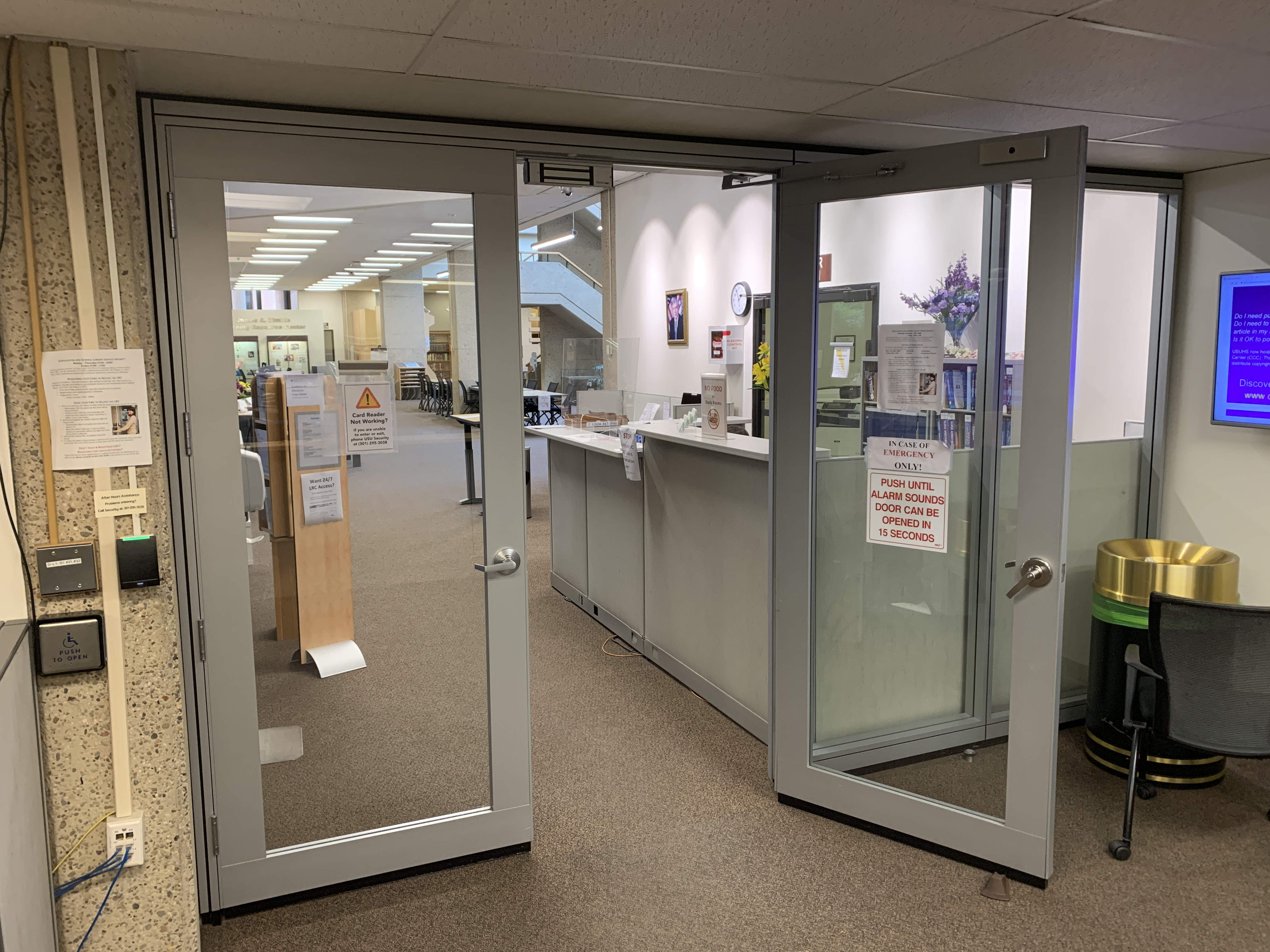 A picture of the front entry doors to the Learning Resource Center. The CAC Reader is to the left of the open door.