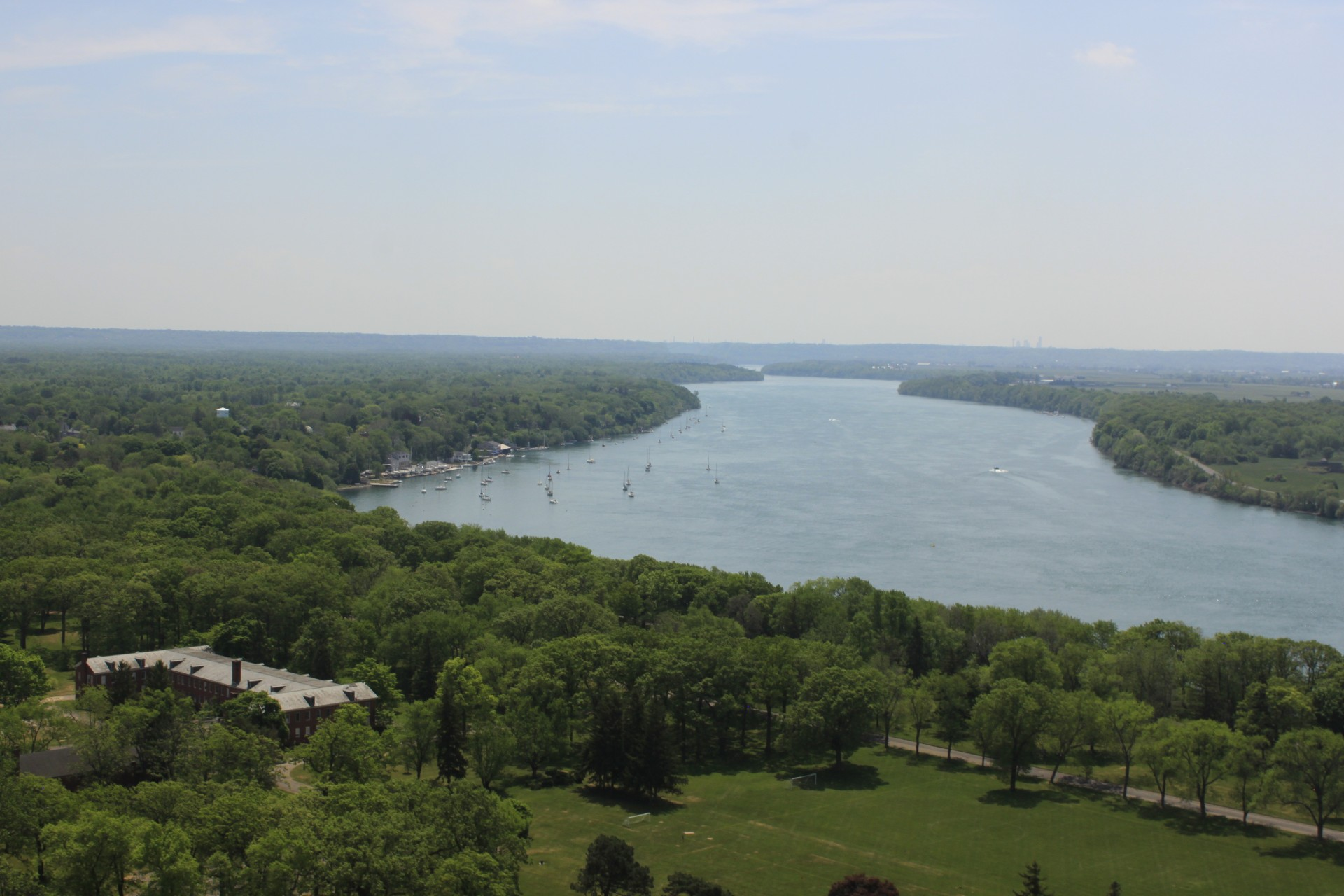 aerial photo showing fort buildings and lake with sailboats