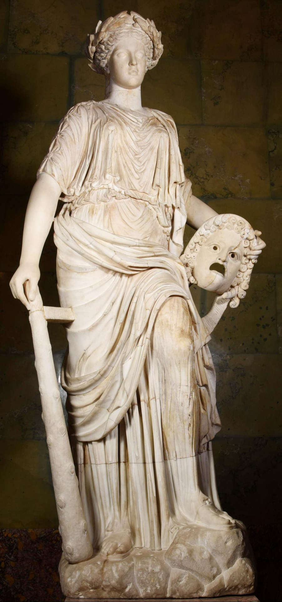 Marble statue of a woman leaning on a club with her right hand and holding a theater mask on her hip.