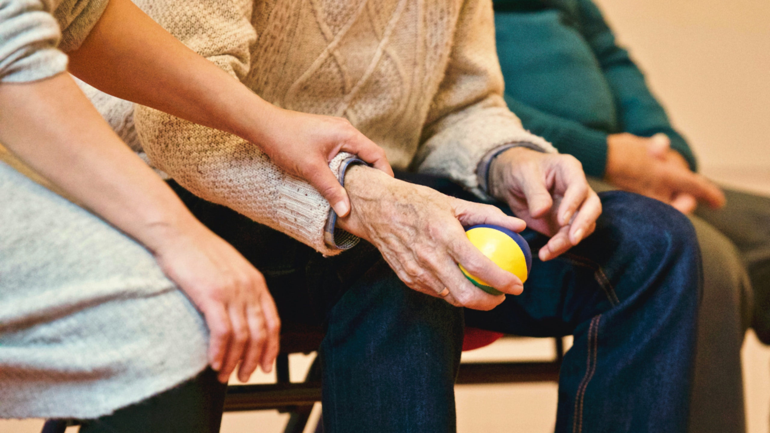 image of a woman reaching out to an elderly person holding a stress ball.