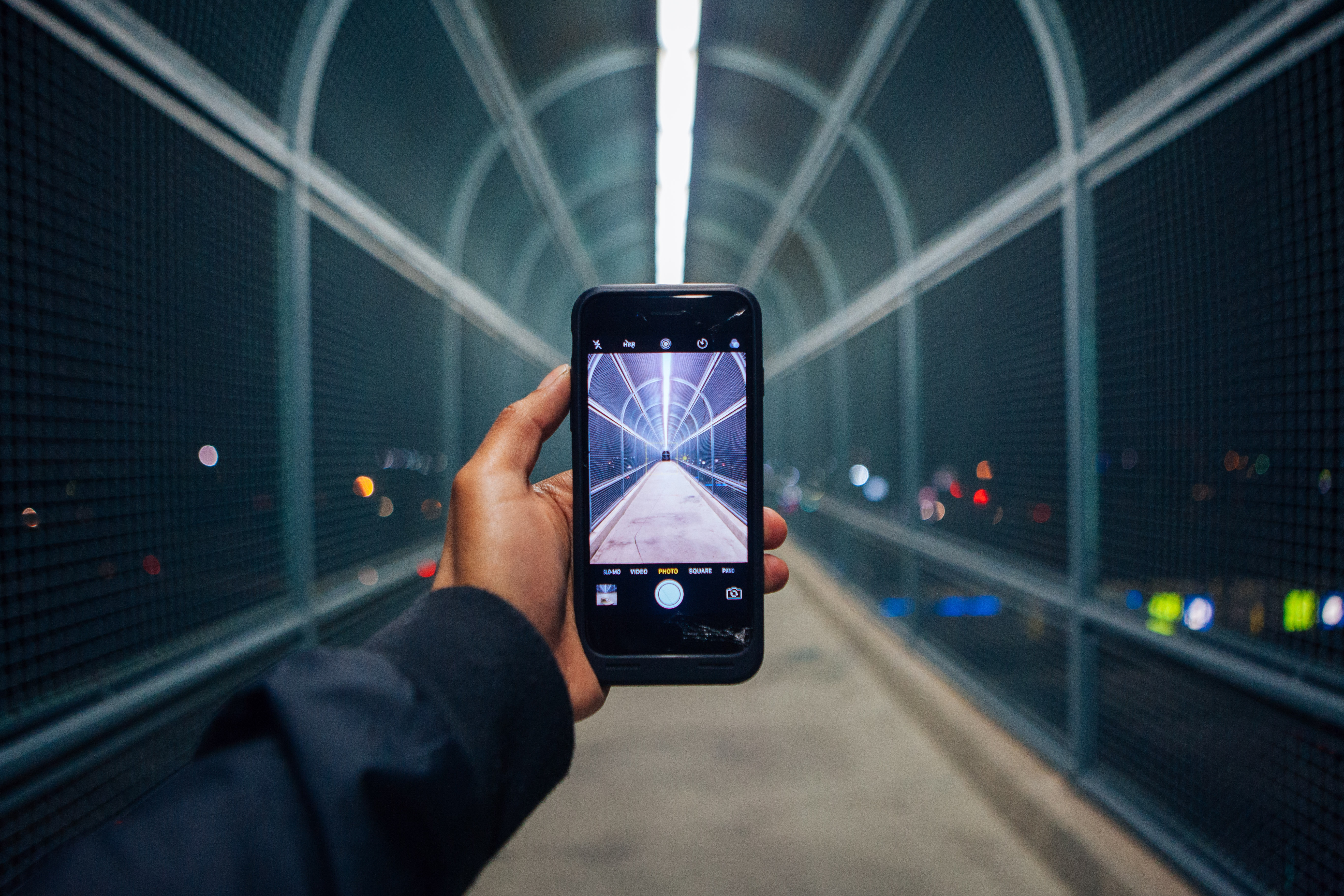 Hand holding a smart phone and taking a photo of a tunnel.