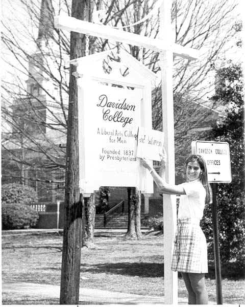 "Photo of the sign at the corner of Main Street and Concord Road, which says ""Davidson College, a liberal arts college for Men, Founded 1837 by Presbyterians""; a female student is standing next to the sign, holding a hand-made sign which says ""and women"""