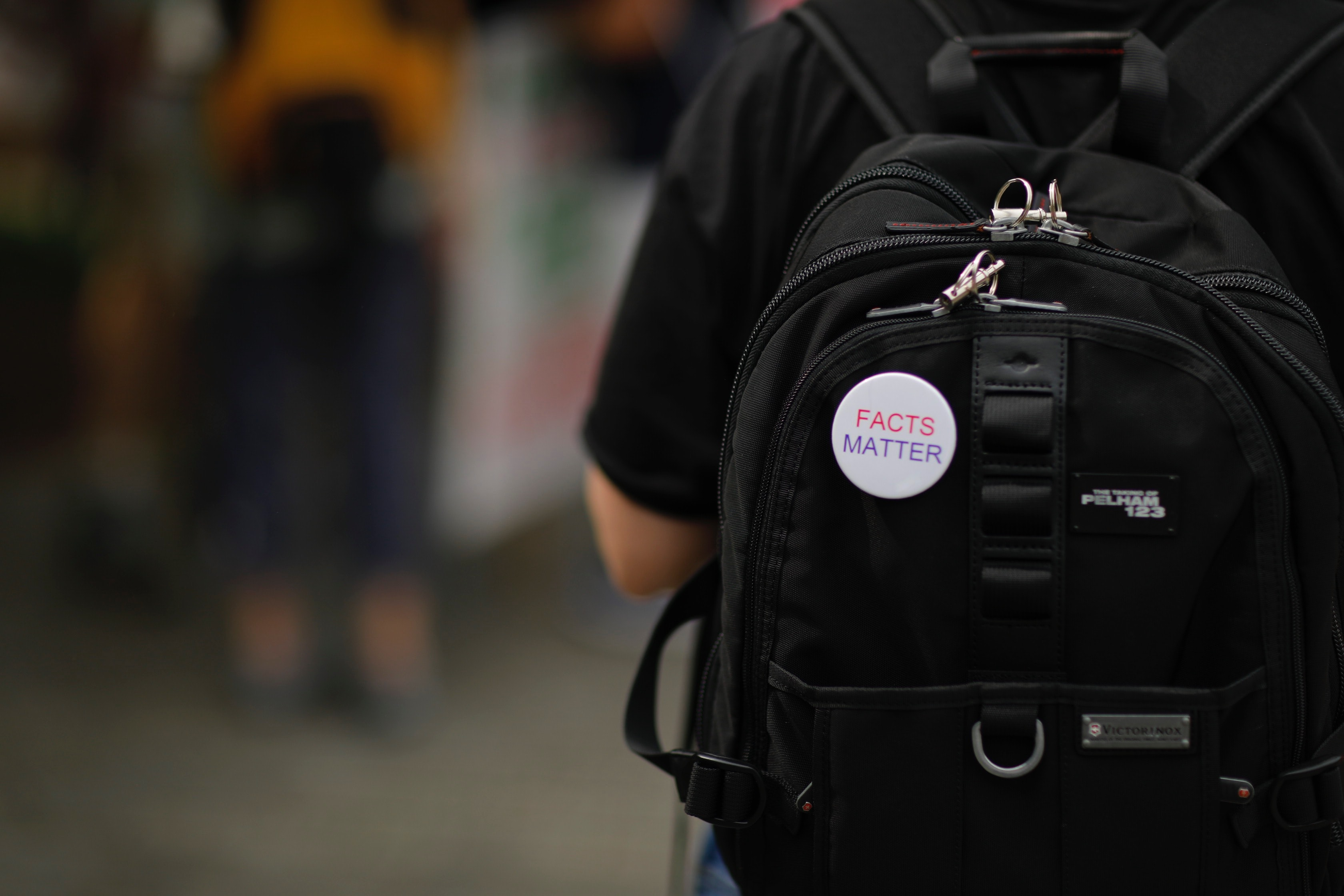 "A ""Facts Matter"" pin on a black backpack.  Image by The Climate Reality Project on Unsplash."