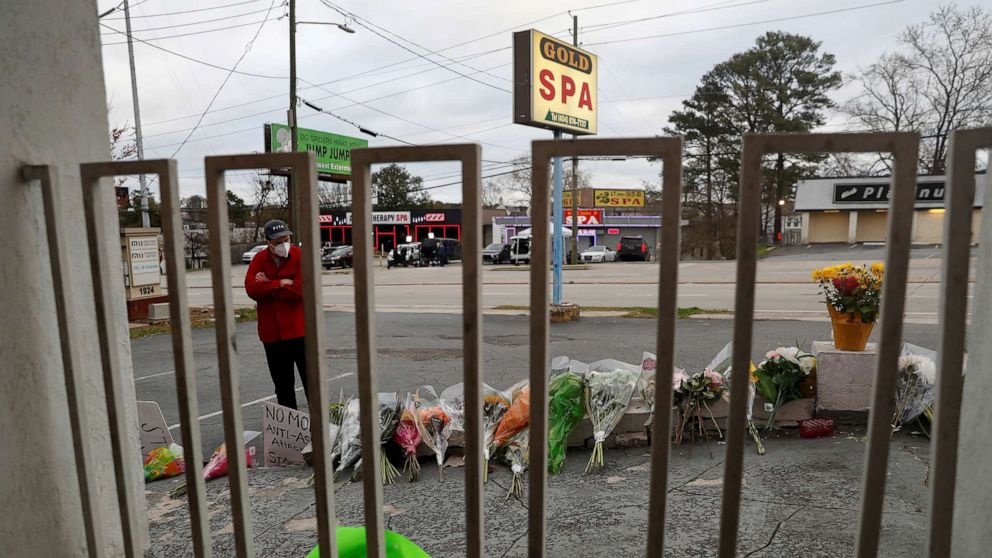 Shannon Stapleton/Reuters Sasha Hasanbegovic looks down after laying flowers at a makeshift memorial outside the Gold Spa following the deadly shootings in Atlanta, March 19, 2021.