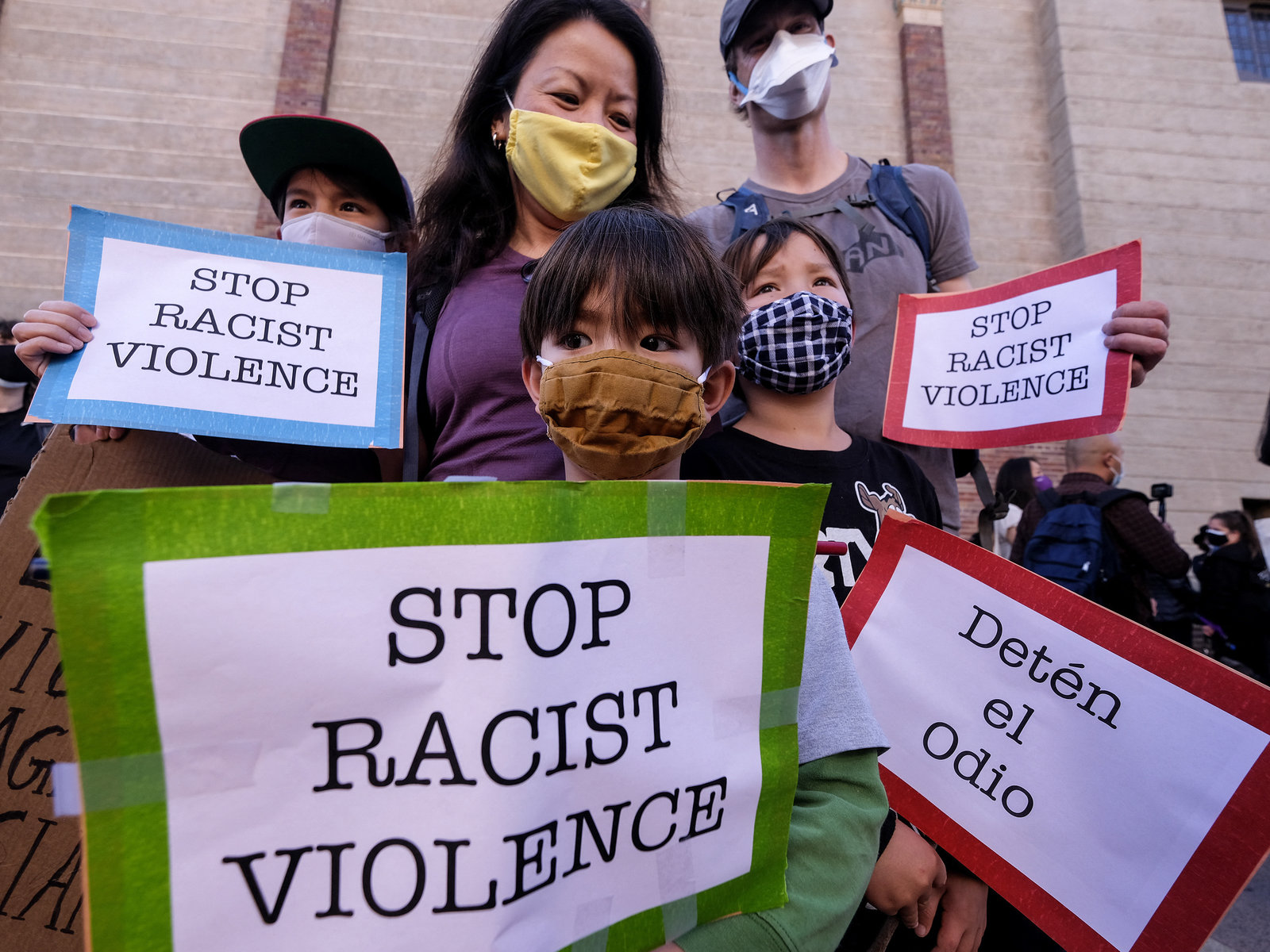 A family wearing face masks and holding signs take part in a rally
