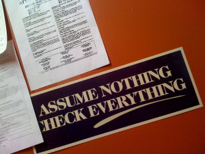 "Photo of papers on a desk, with a bumper sticker reading ""Assume Nothing Check Everything"""