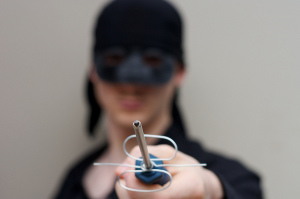 Photo foregrounding a homemade sword held by a man dressed in all black, wearing a mask