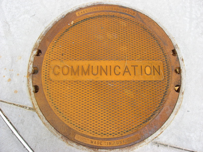 "Manhole cover with ""communication"" written in the middle"