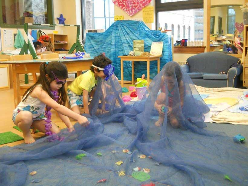 image of small children playing with toys on the floor of a classroom or play area.
