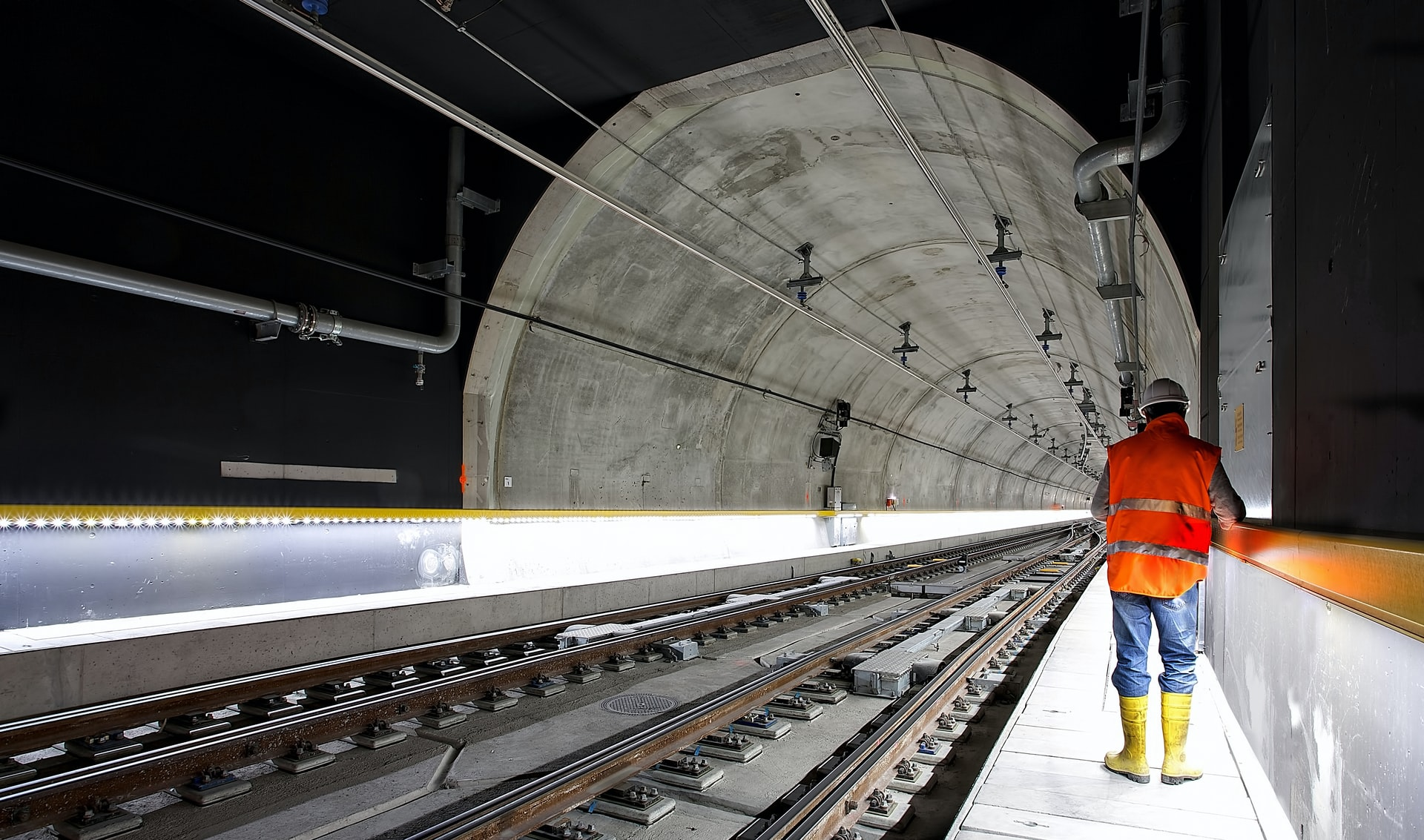 An engineering inspecting a newly-constructed light-rail transit tunnel in Switzerland