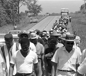 Black and white photo of individuals, primarily African Americans, marching on road