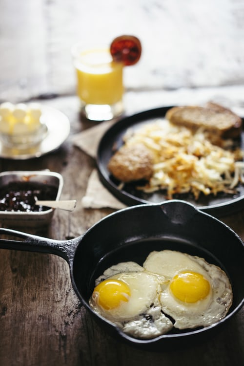 Image of eggs in a pan, hashbrowns, and breakfast