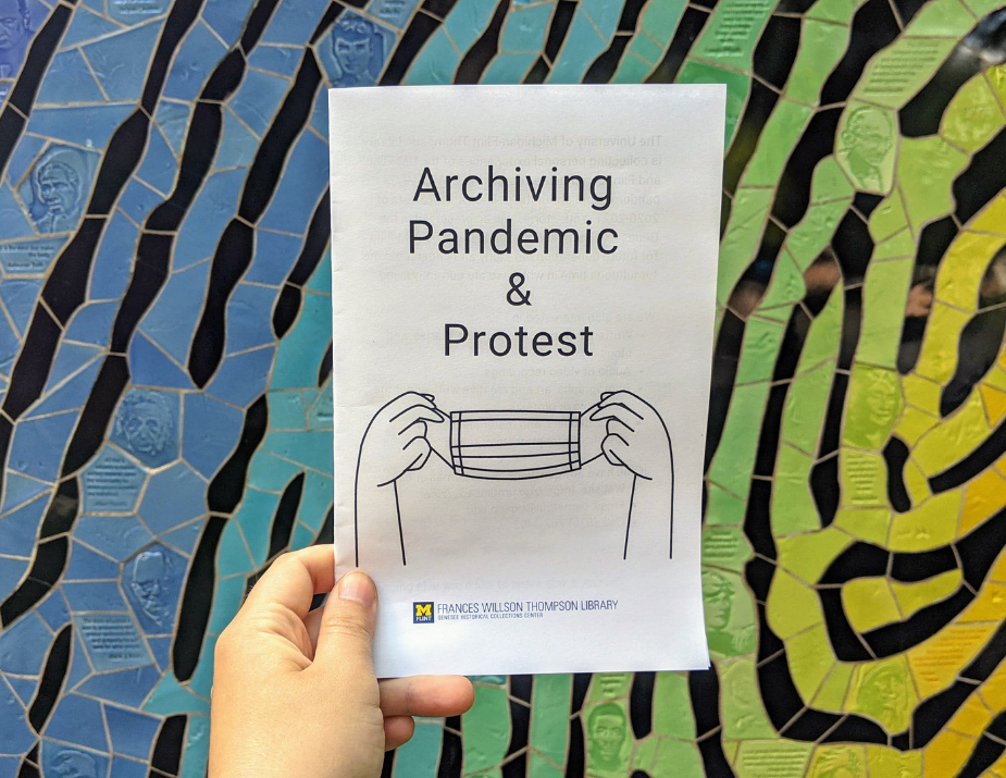 hand holding Archiving Pandemic & Protest zine in front of colorful background