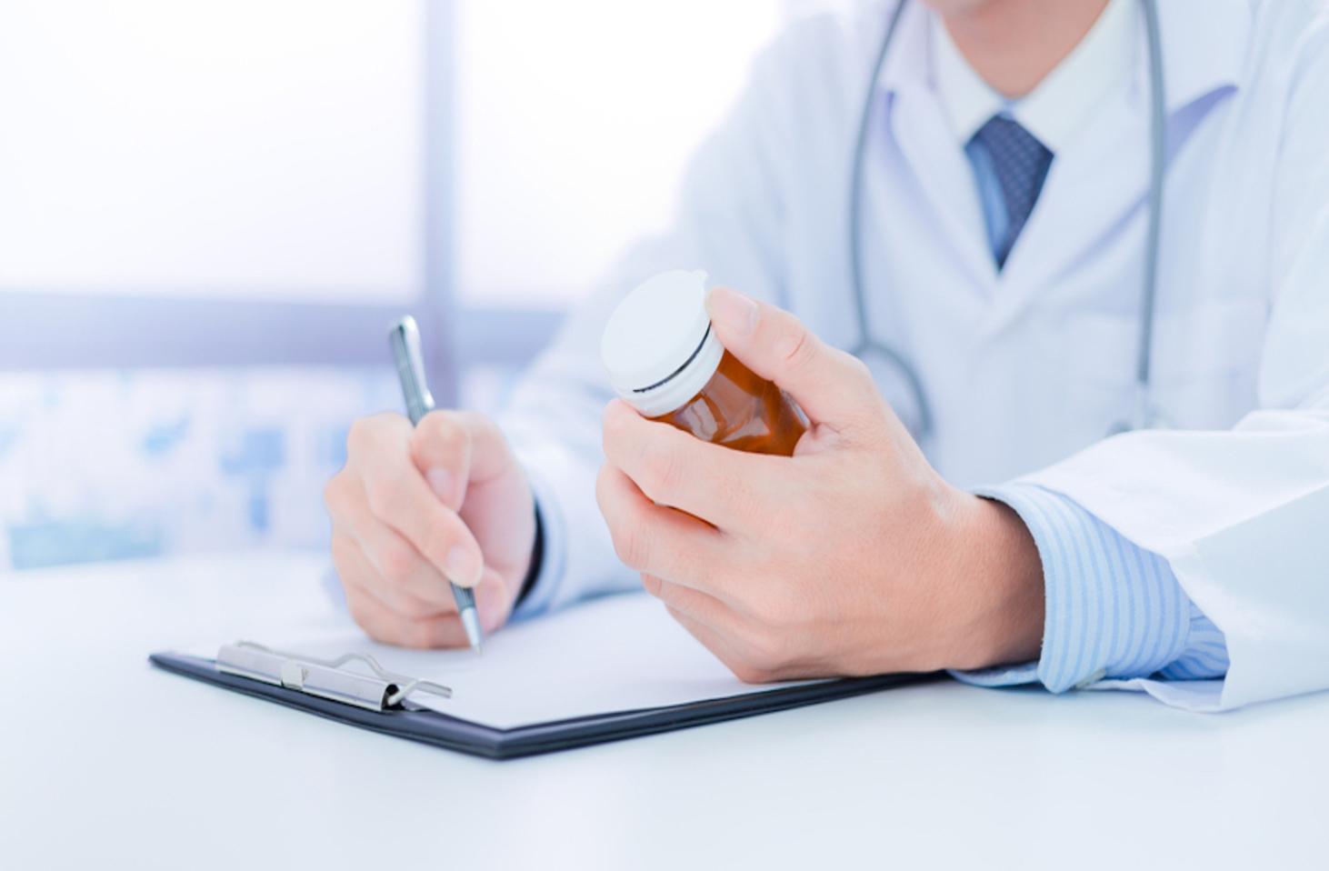 Person in lab coat researching a prescription