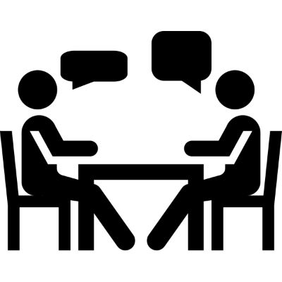 Two people talking on either side of a desk