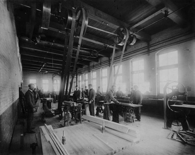 An interior view of students working with early power tools in the old Mechanical Engineering Building. 1898