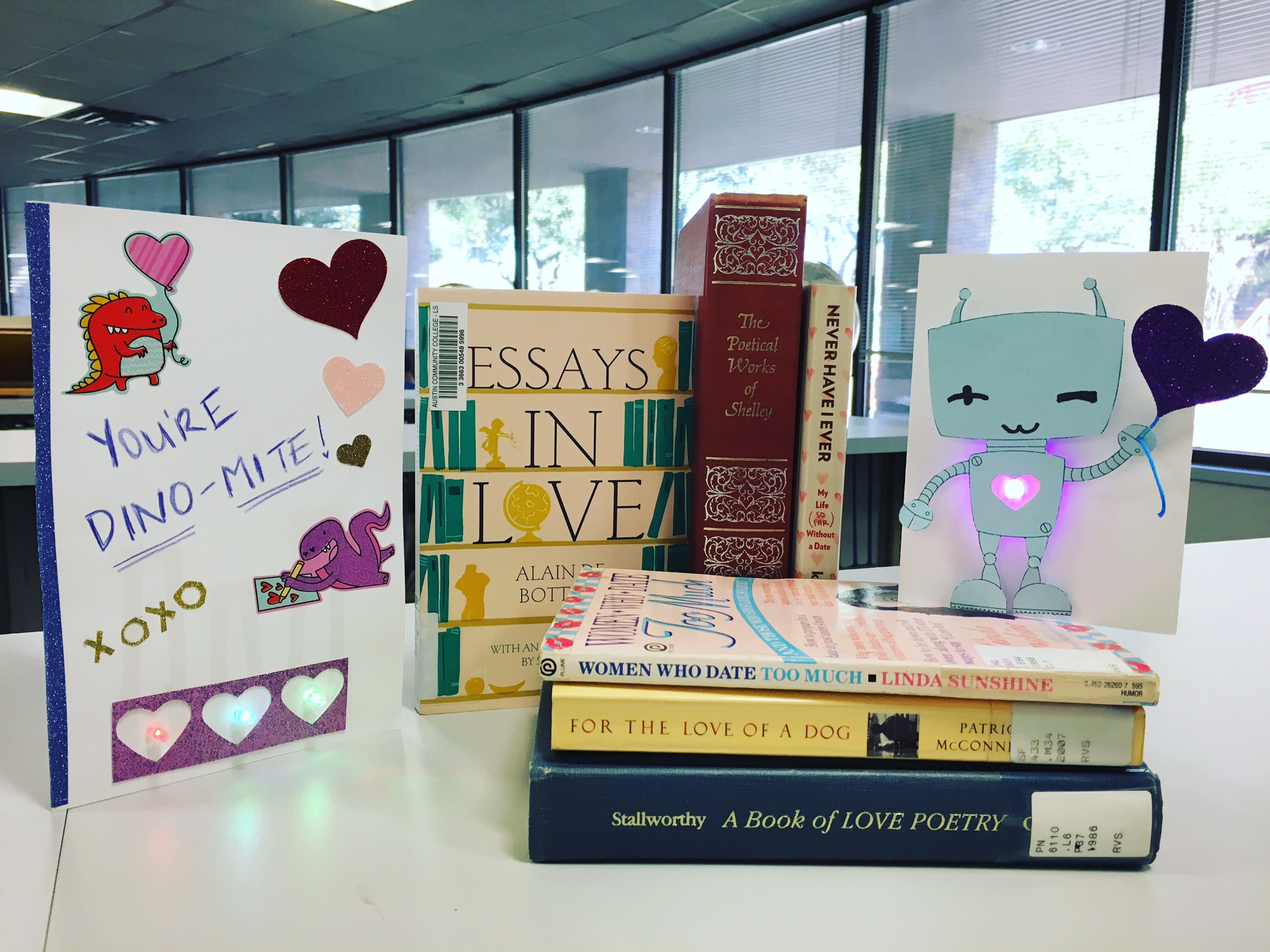 Image of a stacks of books with two paper circuit valentines day cards