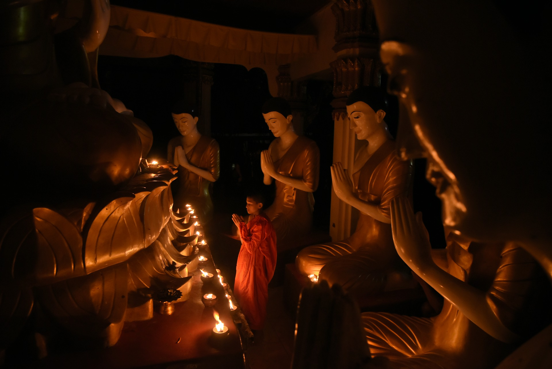 Picture of buddhist praying in front of statues