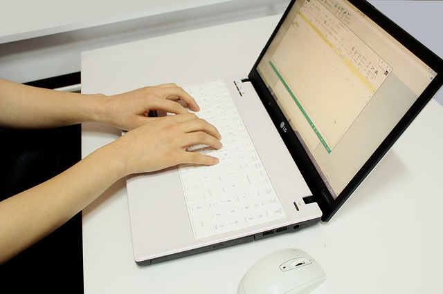 an open laptop on a desk with two hands typing on the keyboard