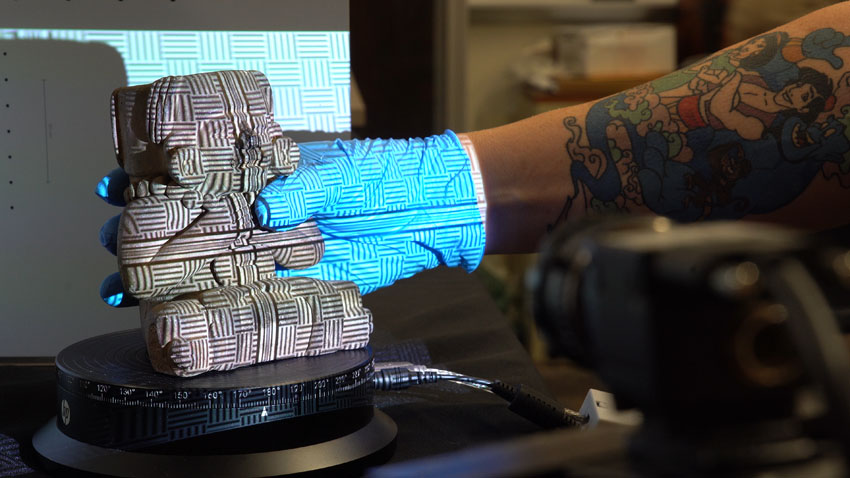 A photograph of an anthropological artifact — a Zapotec urn that has been sculpted into a sitting figurine — being placed on an automated rotating platform by a gloved hand. A 3D scanning system is projecting an alignment grid on the urn and hand.