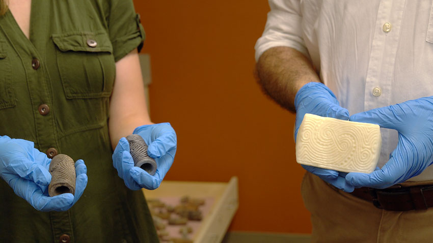 A photograph of two people, each wearing blue examination gloves, holding anthropological artifacts. A woman in a green shirt holds two hollow cylinders in each hand. The cylinders are engraved with a wavy-lined design. A man next to her holds a 3D-printed plastic block with the same wavy-lined design from the cylinders, but in an unrolled form.