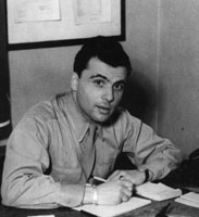 A black-and-white photograph of Robert Behr as a young man, sitting at a desk and writing in a notebook