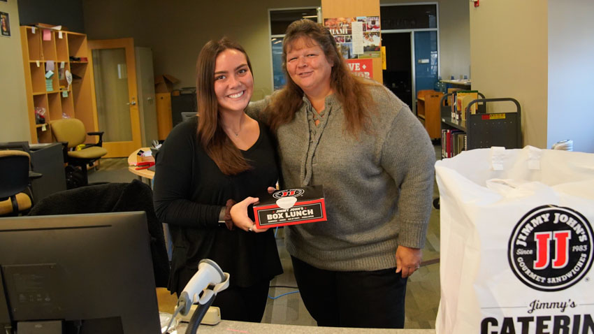 Madison Rossero and Sandy Burwell pose with a boxed Jimmy John's lunch during Student Appreciation Day in 2019