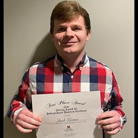 Jack Komer poses with his first-place award certificate.