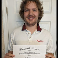 Kyle Laycock poses with his honorable mention award certificate