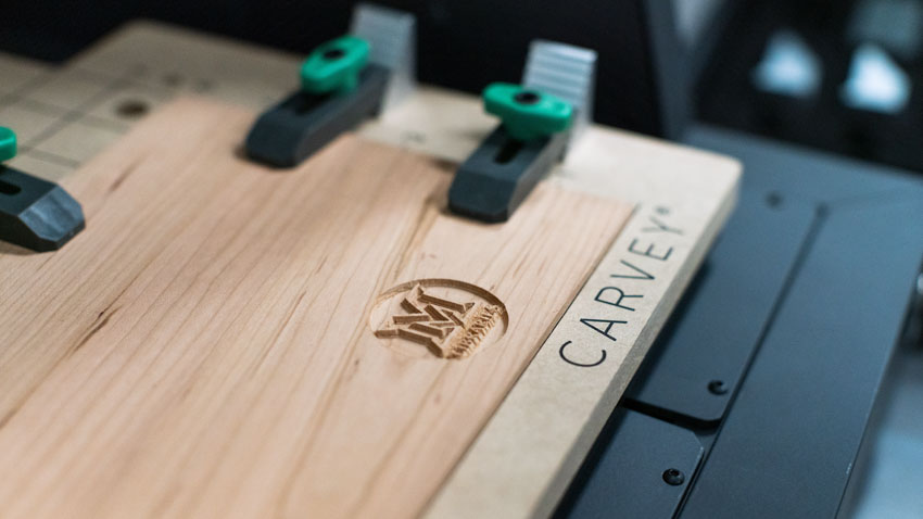 A wooden board is clamped into a Carvey CNC routing machine. The Miami University Libraries logo has been engraved into the wood.