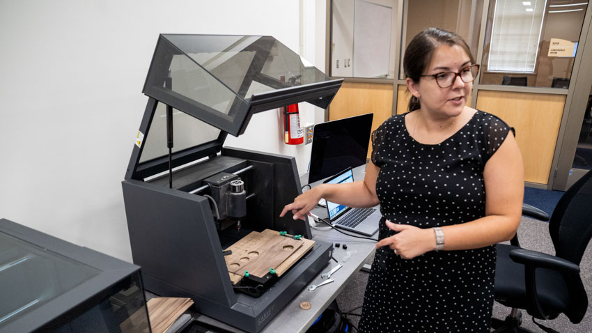 Sarah Nagle gestures to a Carvey, which is an automated routing machine, in the University Libraries Makerspace.