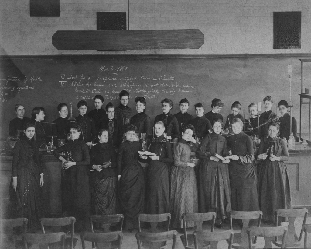 Group of women standing in front of chalkboard, Ellen Swallow Richards (back row, far left)