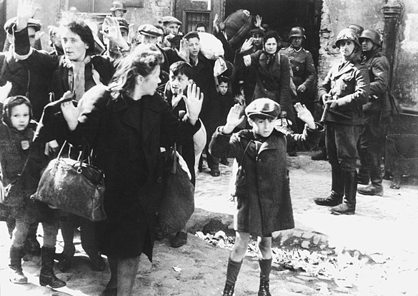 Photograph taken during the 1943 Warsaw Ghetto uprising, a boy holds his hands over his head while SS-Rottenführer Josef Blösche points a submachine gun in his direction