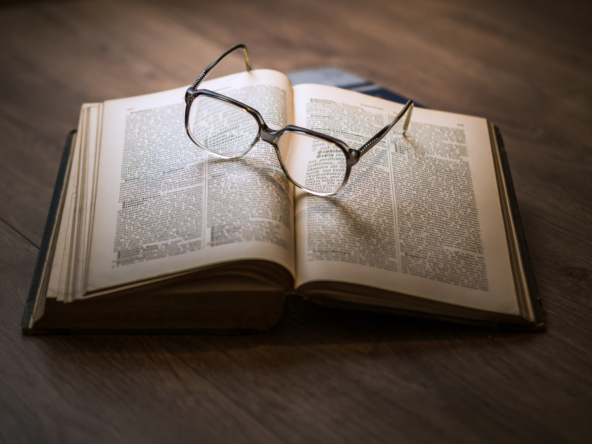 Open book with glasses laying on top