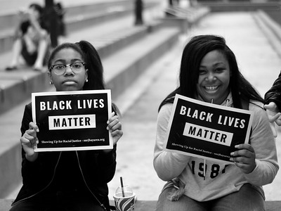 "two Black university student holding ""Black Lives Matter"" sign"