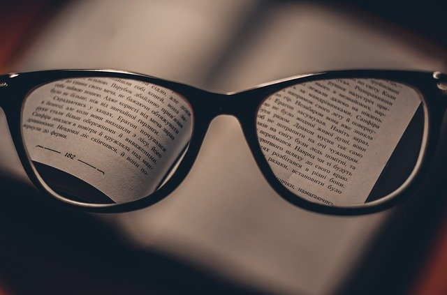 Pair of dark glasses focusing in on the words to a book.