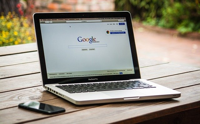 Open laptop with Google hompage on it, sitting on a wooden table.