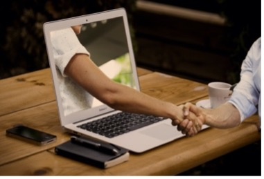 Handshake, with one hand coming out of a computer, to the person at the desk.