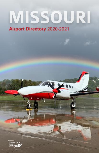 Red and white airplane on a runway with a rainbow in the background