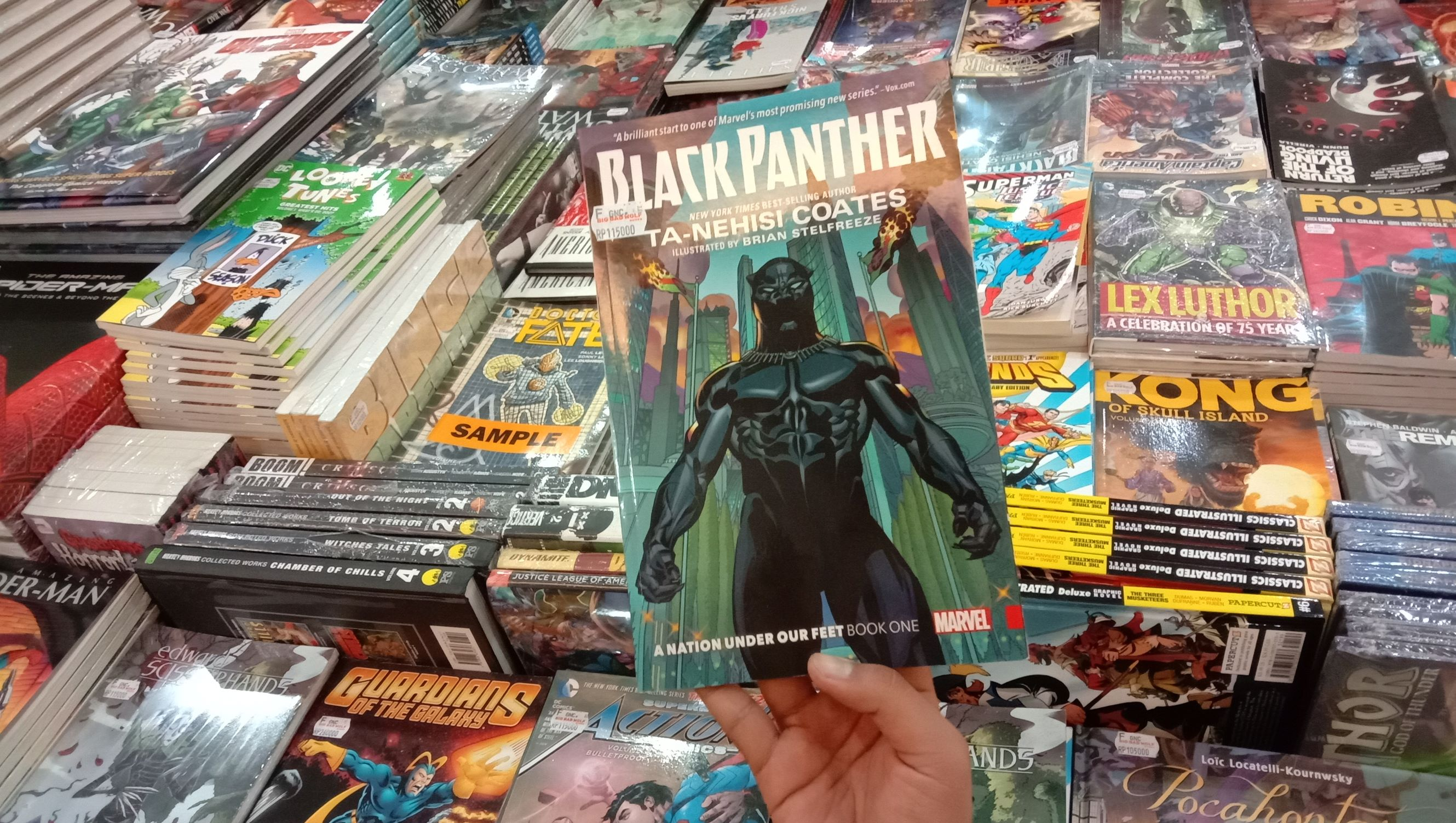 Hand holds Black Panther comic over a table of stacks of other comic books.