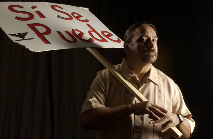 Tony Garcia is the artistic director and dominant force at El Centro Su Teatro, based in the former Elyria Elementary School. He writes plays, directs theaters and also hosts music, film and art events with a Hispanic focus.  He is holding a sign, with the slogan, in spanish, that translates into