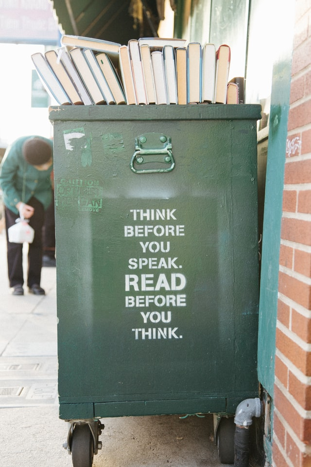 Think before you speak. Read before you think spray painted on a trashcan.