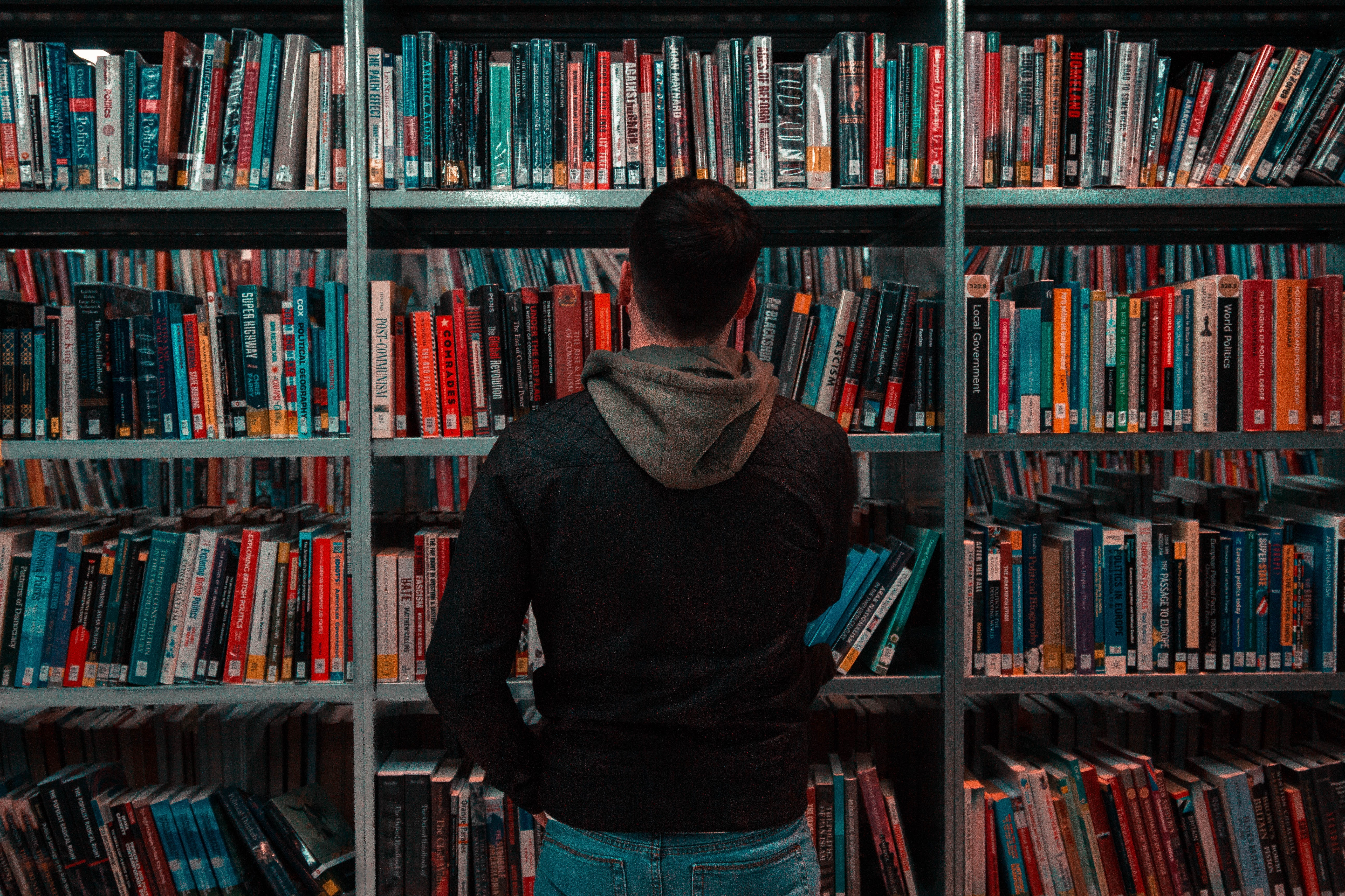 man in front of bookshelf in a library