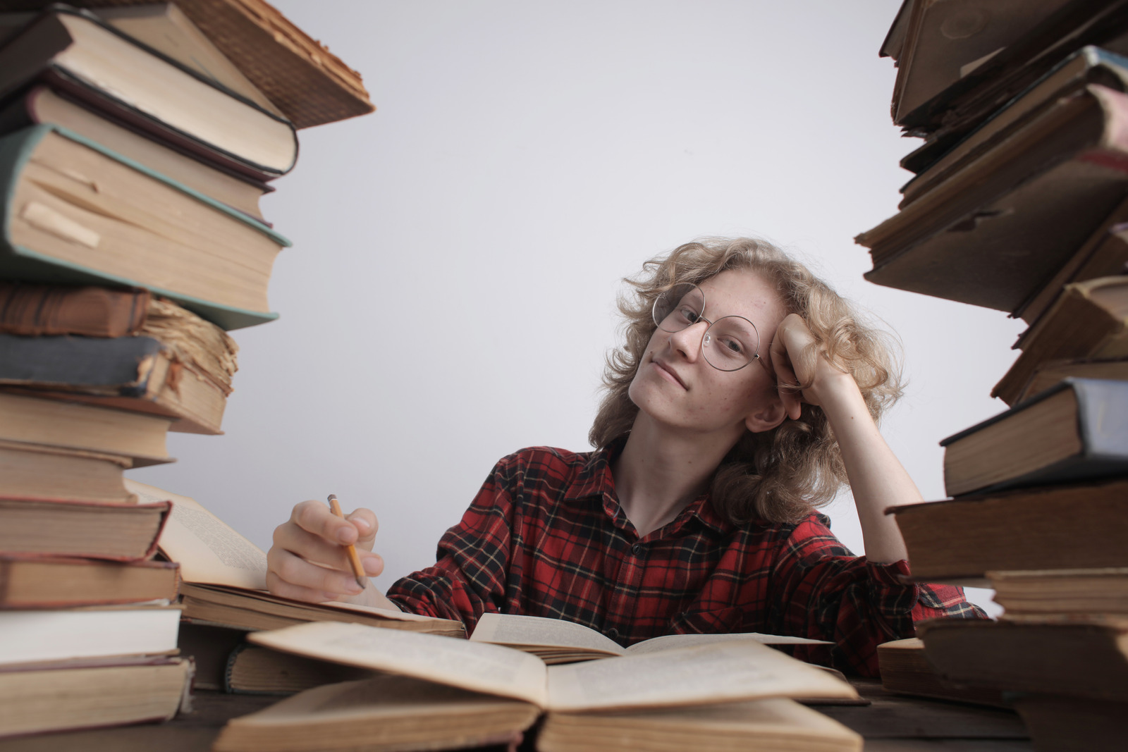 person at desk surrounded by stacks of books